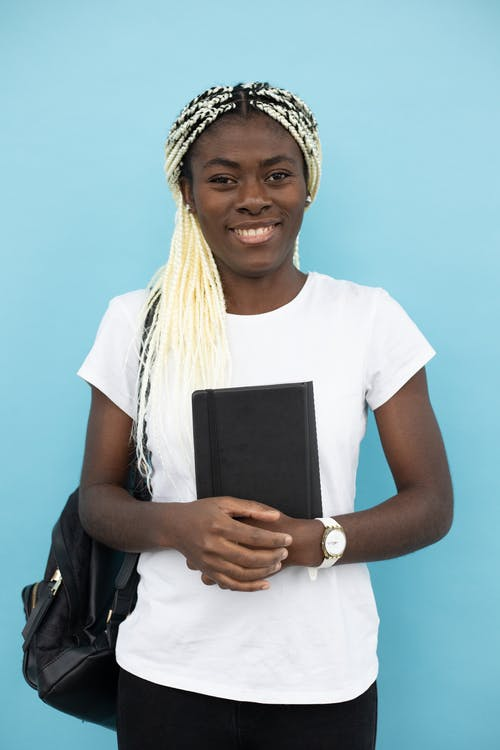 Cheerful black woman with notebook and backpack