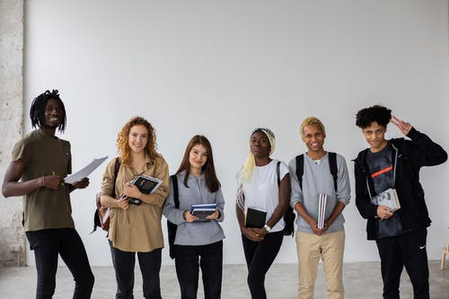 Group of smiling multiracial classmates standing with books and backpacks and smiling widely at camera