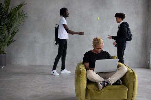Serious black man using laptop while classmates playing with ball