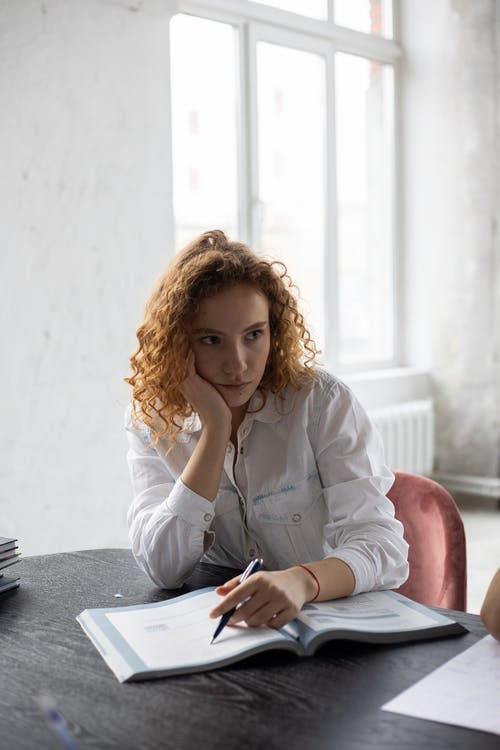 Weary female student with curly hair leaning on hand sitting with pen and opened book during studies
