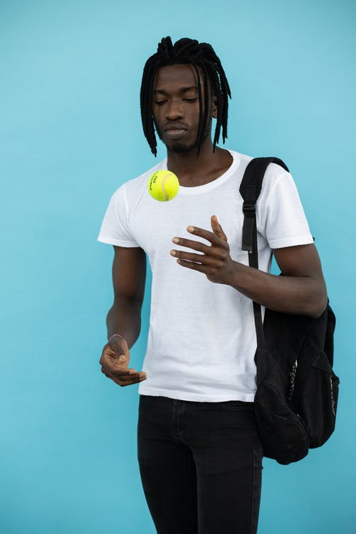 Concentrated black man with tennis ball