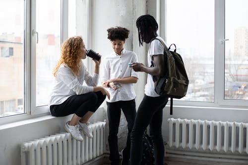 Group of diverse students drinking takeaway coffee and browsing smartphones while standing near window in classroom before lesson in college