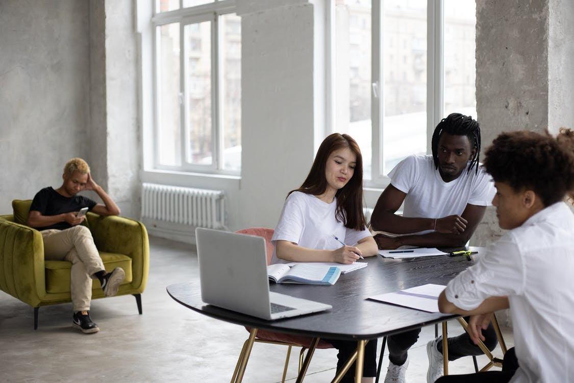 Group of young multiethnic coworkers in casual clothes gathering at table with laptops and papers and discussing project details in light spacious workspace