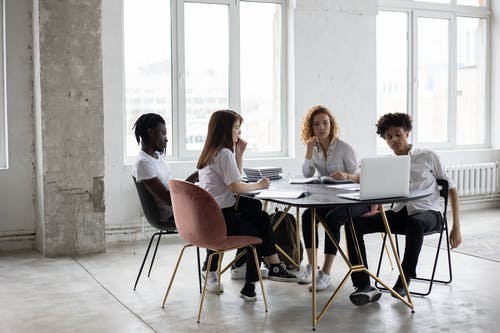 Full length concentrated multiethnic coworkers in formal wear working on project together and gathering at desk in light loft workplace