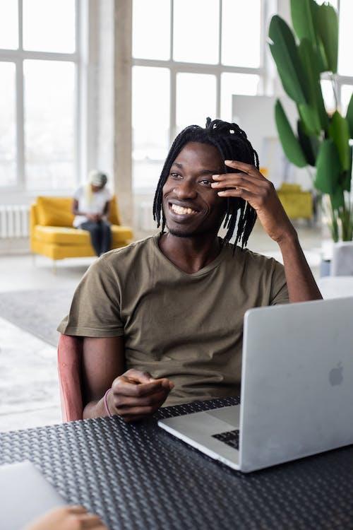 Hombre En Camiseta Marrón Con Cuello Redondo Sentado En Una Silla Frente A Macbook
