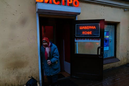 Senior gloomy female in shawl and warm jacket with cup of coffee leaning on entrance of bistro and looking at camera