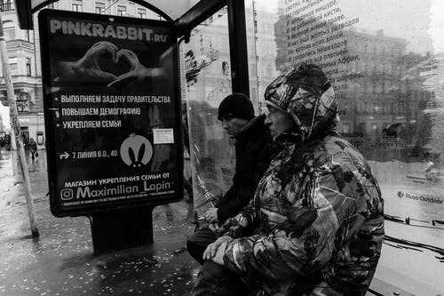 Black and white side view of sad thoughtful exhausted males wearing jacket with hood and winter hat and waiting bus on bench in rainy autumn