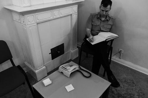 Focused policeman sitting on chair and writing in book