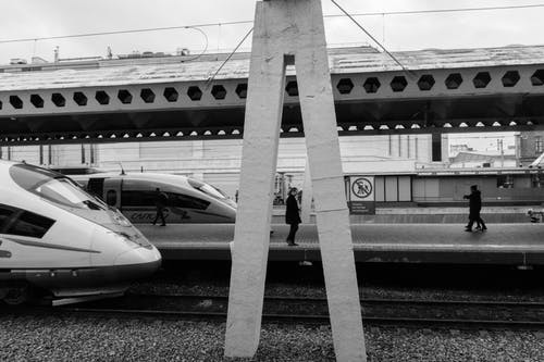 Black and white of station with speed locomotives on railroad and passengers walking along platform and stone support construction in center of image