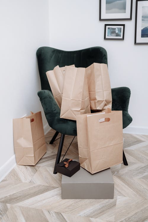 Brown Cardboard Box on Green and Black Chair