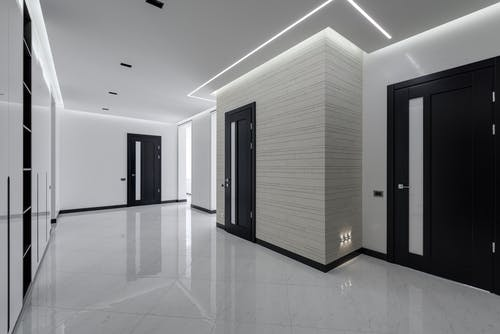 Modern spacious corridor with white walls and floor and black doors and ceiling decorated with LED lights