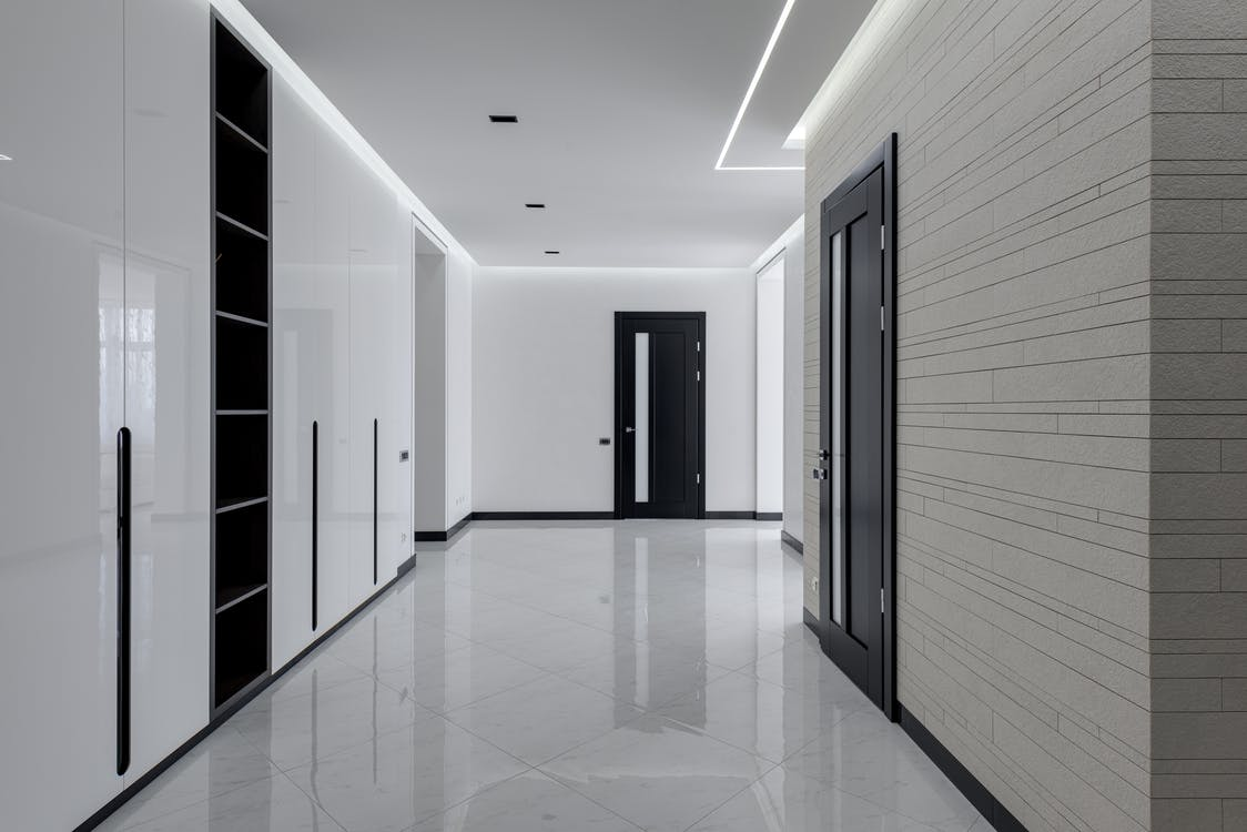 Wide corridor in modern house with white tiled walls and floor black wooden doors and shelves for storage built in wall