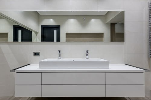 Stylish bathroom with mirror over white table with double vessel sink and towel warmer