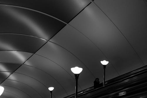 From above of escalator area with lonely silhouette on stairs illuminated with shiny bulbs under round metal ceiling construction