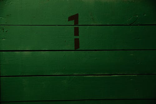 Background of plank wall of green grass color with black simple inscription representing numeral made with template