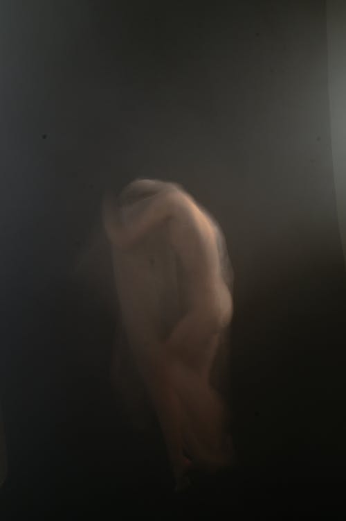 Nude woman in dark room tilted head