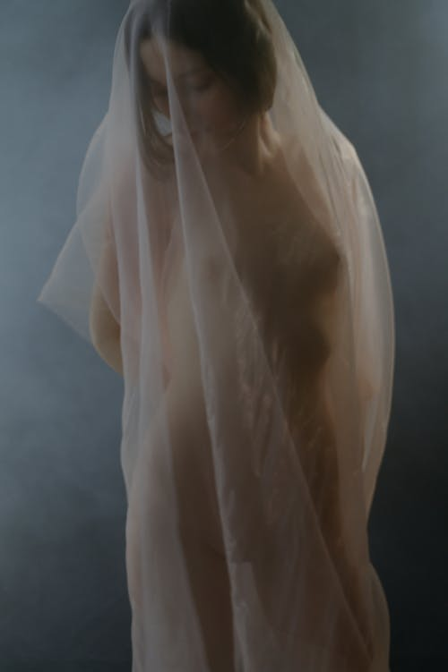 Naked woman putting head down under translucent fabric