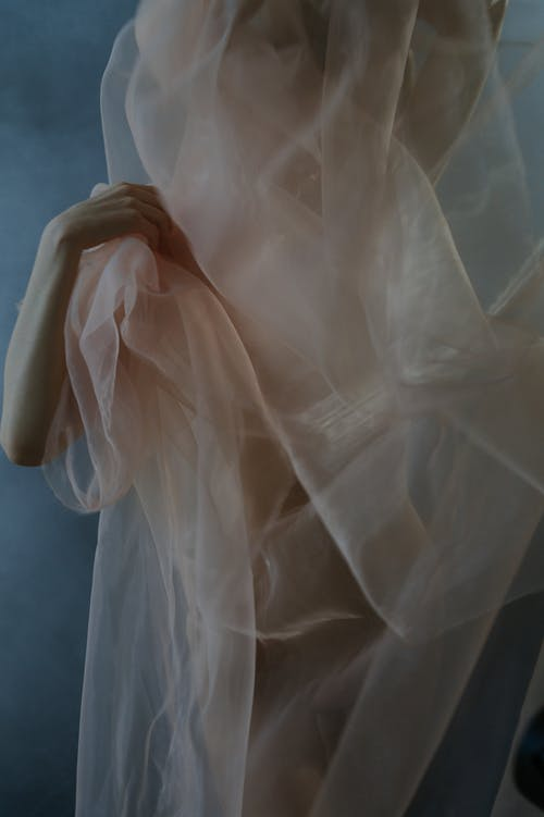 Crop anonymous female model covering naked body with translucent fabric and holding material with gentle hand