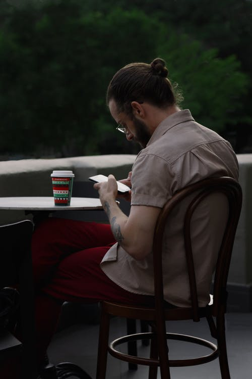 Young man surfing internet on smartphone in cafe