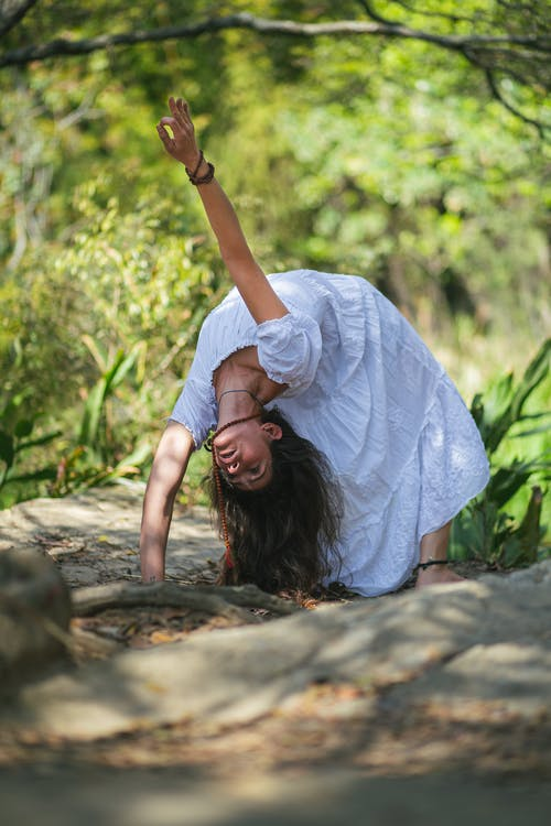 Flexible woman doing Wheel posture with arm raised