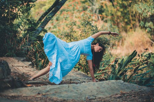 Full body of barefoot female in dress doing lateral bend supported by leg and arm in nature during yoga session