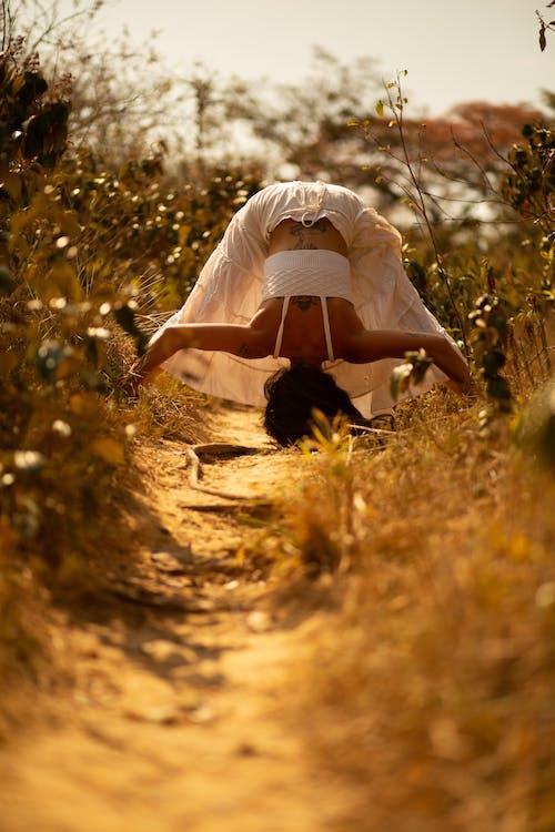 Woman doing Prasarita Padottanasana in nature
