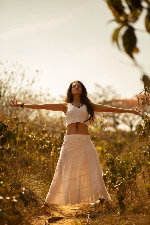 Graceful woman with outstretched arms in nature