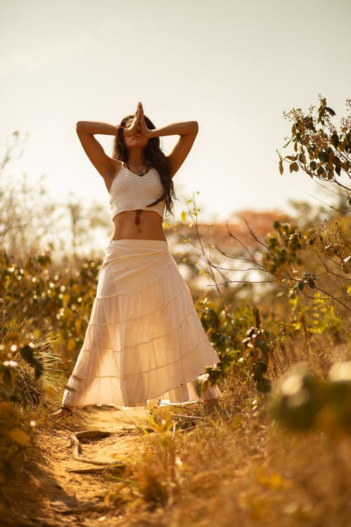 Full body of peaceful female in white summer outfit standing among plants with hands together during meditation