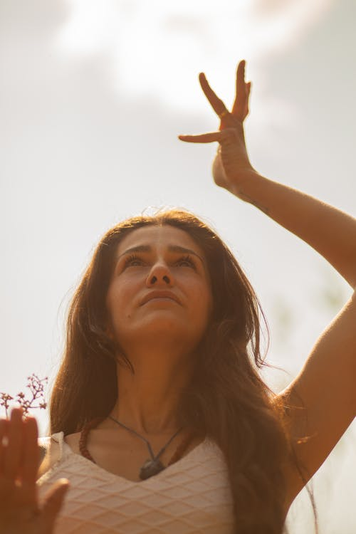 Low angle of graceful female with raised arm standing in nature and doing yoga while looking up