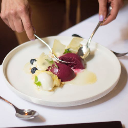 Crop anonymous female eating mousse dessert with blueberries and sauces on white plate while using spoon and fork at table