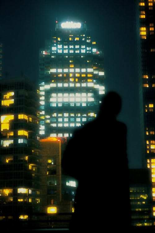 Silhouette of anonymous man near illuminated buildings in evening city