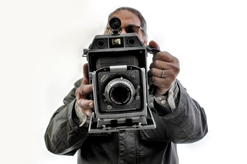 Man in Gray Jacket Holding Black and Silver Camera