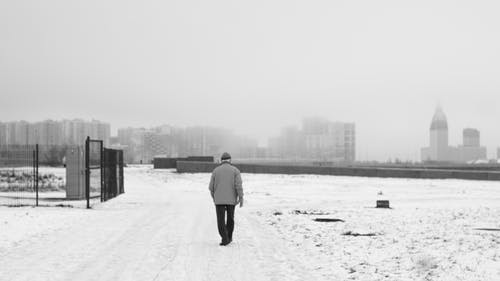 Unrecognizable man walking on pathway in winter city