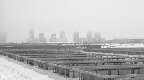 Black and white of industrial constructions in rows on snowy land against multistage buildings in town