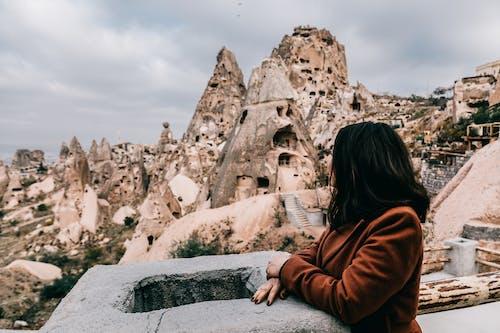Unrecognizable woman enjoying view of ancient buildings