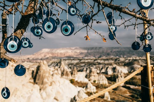 Amulets made of blue glass reminding eye hanging on tree branches in Cappadocia