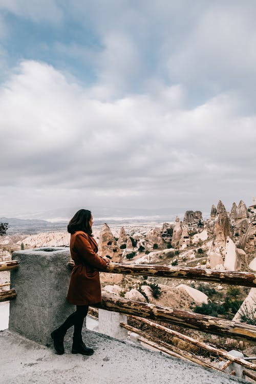Full body side view of unrecognizable female tourist in casual wear standing on viewpoint and admiring landscape