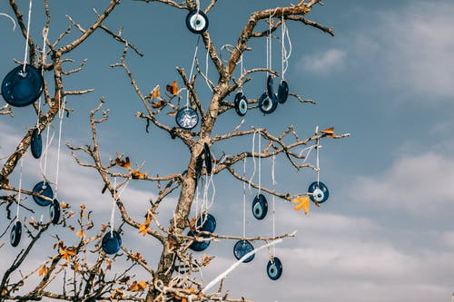 From below of traditional blue eye shaped nazar amulets protecting form evil eye hanging on leafless tree branches against cloudy blue sky in Cappadocia