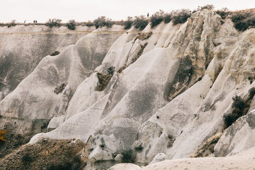 Massive rocky formation with dry plants on peak under overcast sky