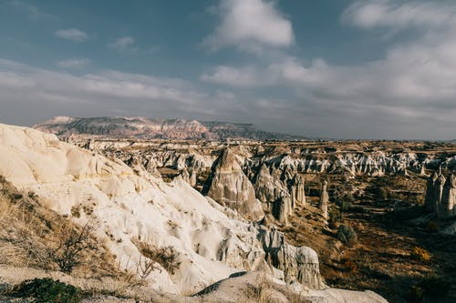 Various massive fairy chimney rock formations surrounded by cliffs against cloudy blue sky in Cappadocia