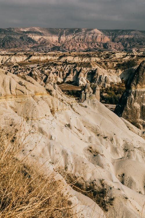 Spectacular landscape of dry uneven mountains with sand and grass in valley in summer day under gray cloudy sky