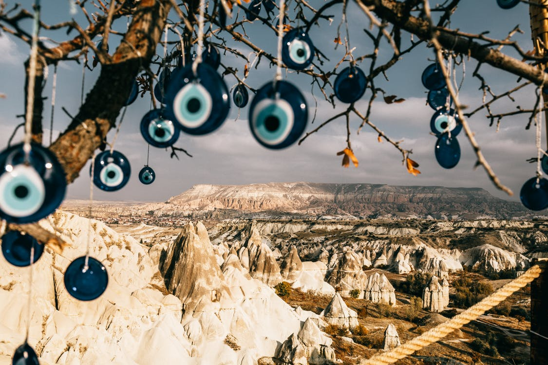 Nazar amulets on threads hanging from tree branches near rocky uneven formations with mountains and grass with plants in Turkey in Cappadocia region under gray cloudy sky in summer day