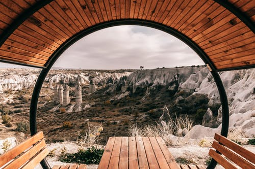 Bench with roof near stony formations and hills in Cappadocia