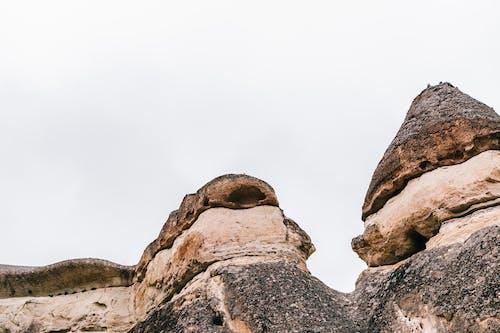 Heavy stones on rocky formation under gray sky