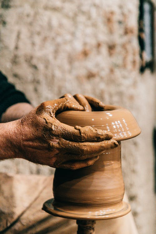 Crop anonymous craftsman doing pottery with clay and special equipment on blurred background