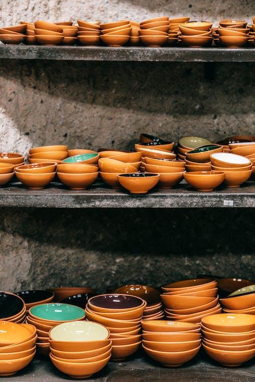 Many shiny ceramic colorful bowls on shelves