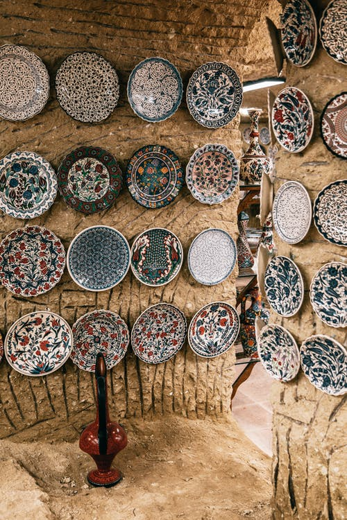 Many oriental plates with different ornaments decorating rough stone walls in daytime in Morocco