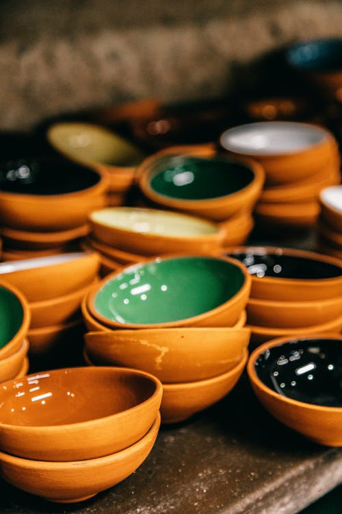 Many bright ceramic empty bowls placed on shelf in local market of town