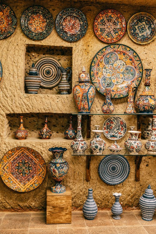 Collection of various decorative ceramic plates and vases placed on rough stone wall and floor
