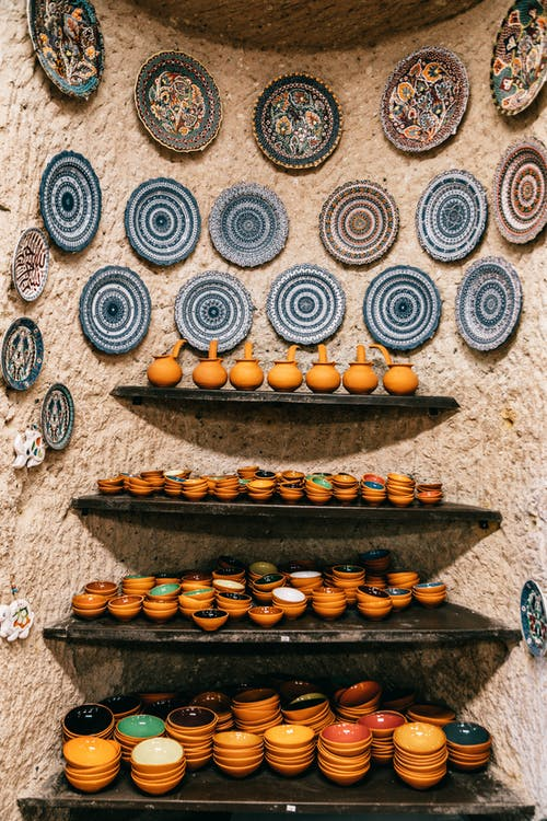 Shelves with different ceramic bowls near stone wall